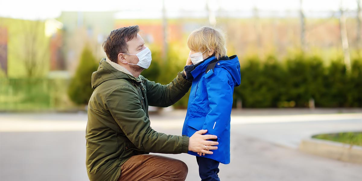 Father helping son with mask