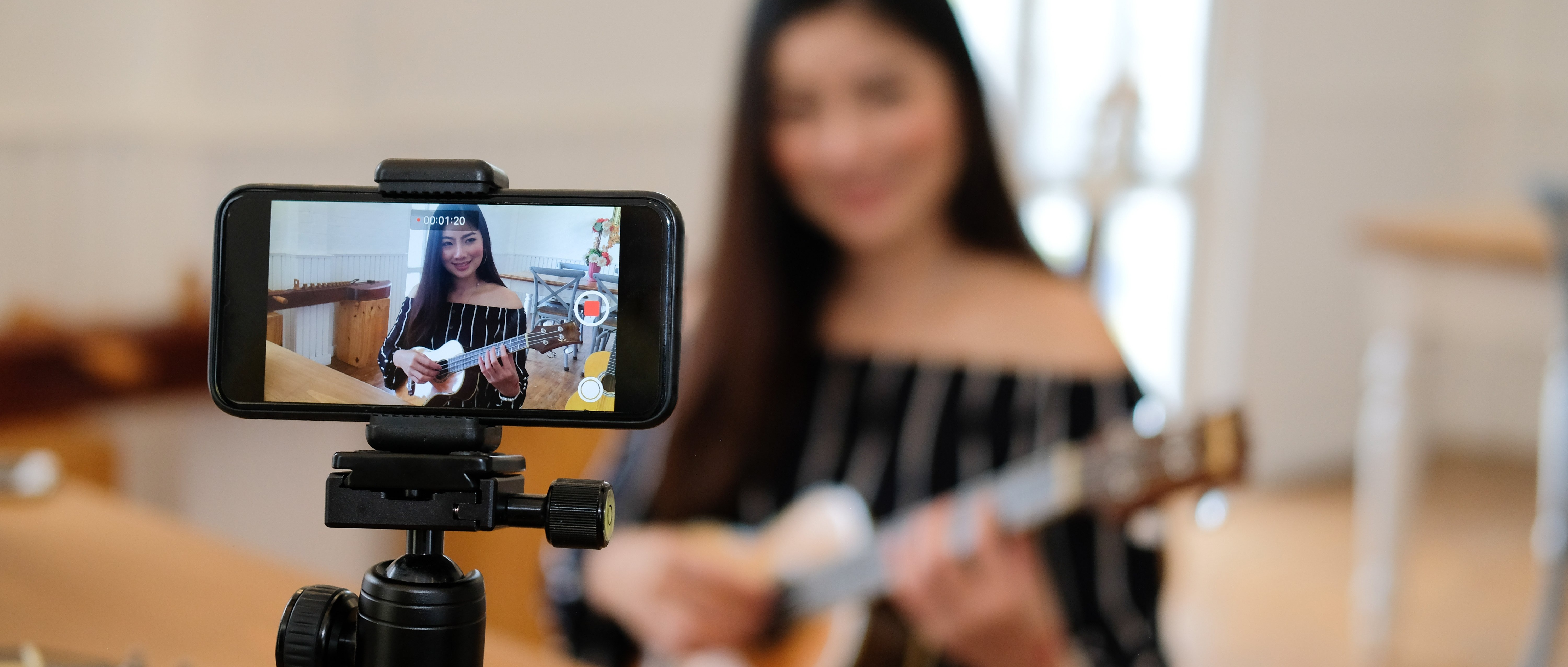 Woman recording herself playing guitar with a smartphone