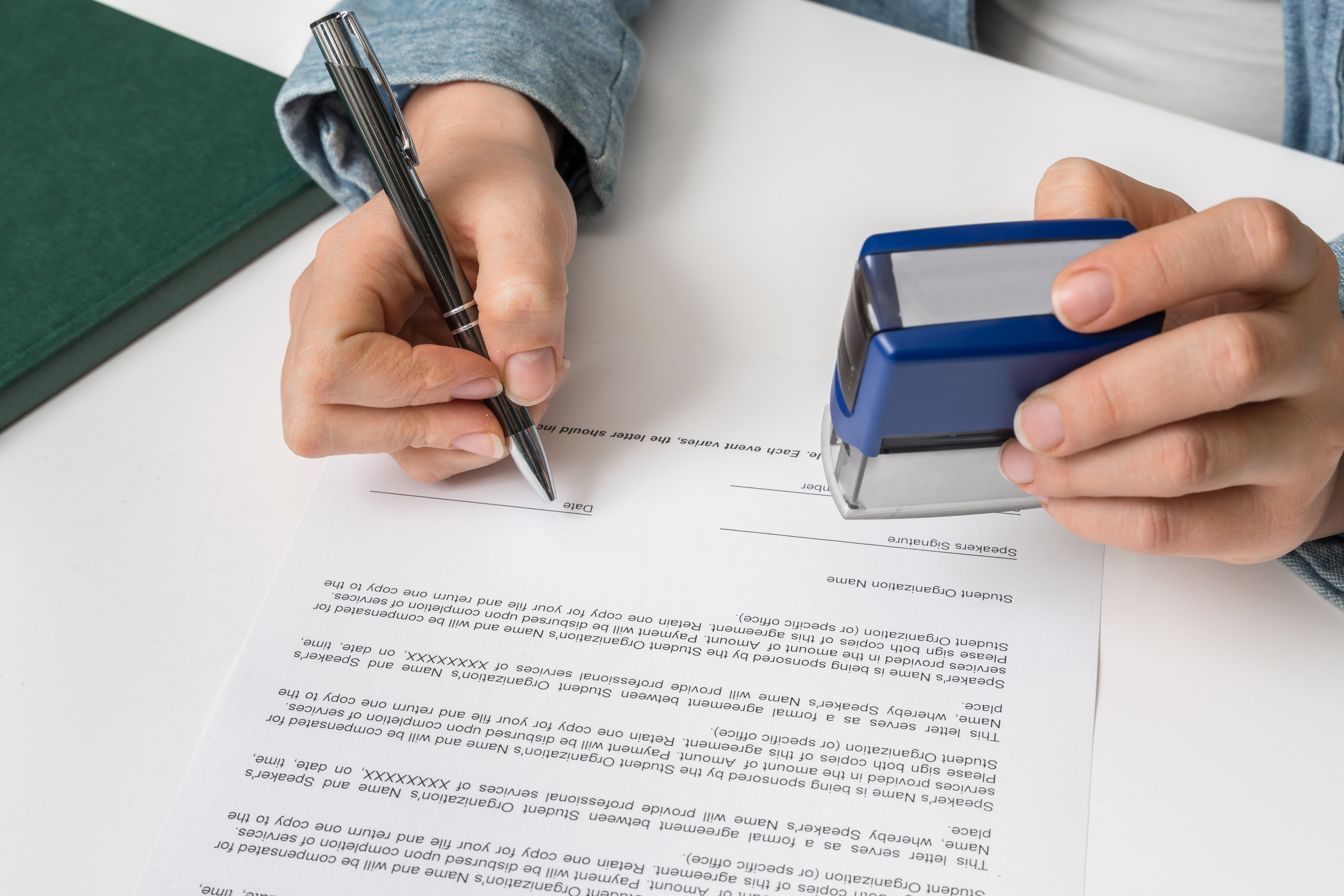 a hand holding a pen signing a document